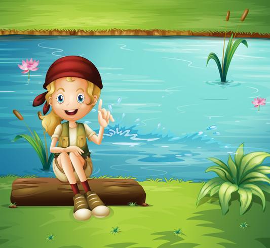 Una niña sentada sobre un tronco a la orilla del río