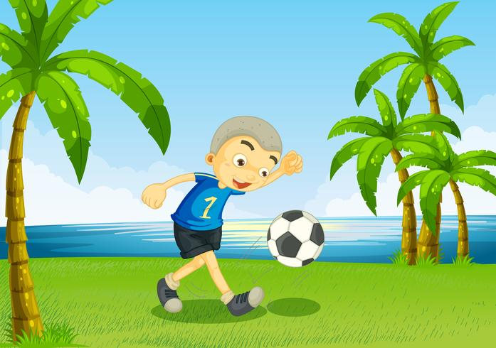Ein junger Fußballspieler am Flussufer mit Palmen