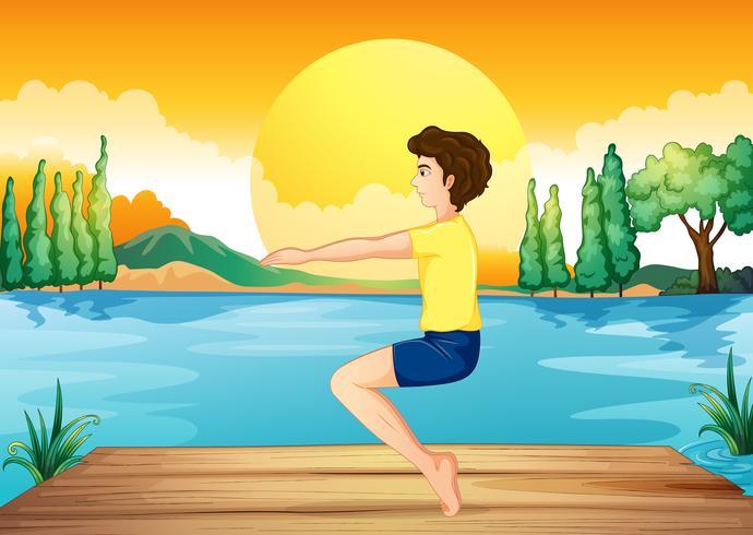 Un niño haciendo ejercicio cerca del río profundo.