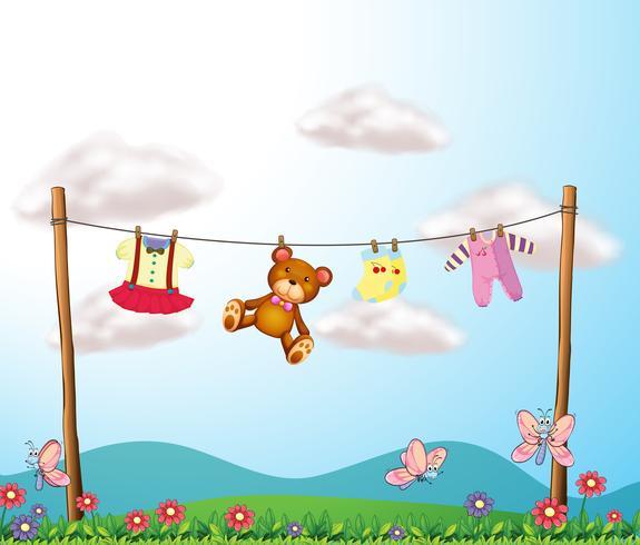 De kleding van een kind hangt met een teddybeer