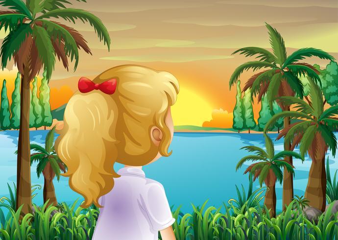 Een meisje dat op de zonsondergang bij de rivieroever let