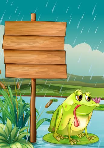 Un letrero vacío y una rana bajo la lluvia.