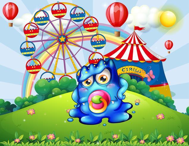 Un bébé monstre au sommet d'une colline avec un carnaval