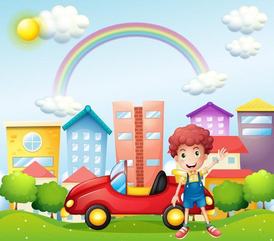 Un niño y su carro rojo cerca de los altos edificios.