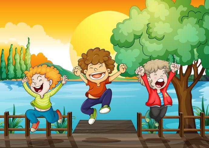 Trois garçons heureux au pont de bois