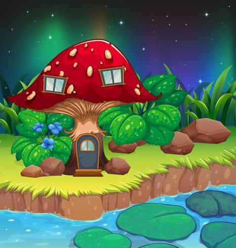 Una casa dei funghi rossa vicino al fiume con ninfee