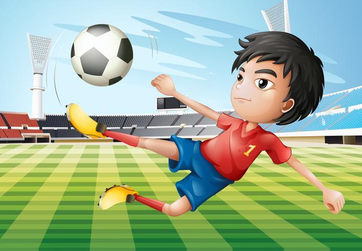 Ein Junge, der Fußball am Fußballplatz spielt