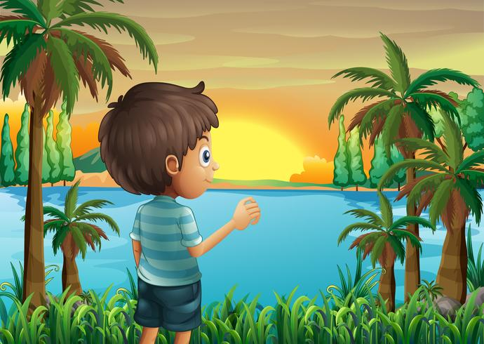 En pojke som tittar på solnedgången vid flodbredden