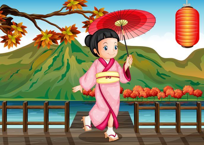 Una dama vistiendo un kimono rosa con un paraguas.