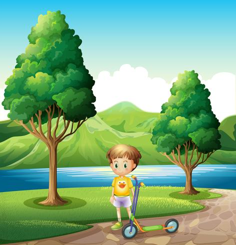 En ung pojke med en scooter som står nära floden