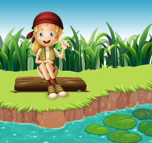 Ein Mädchen, das auf einem Holz entlang dem Fluss sitzt