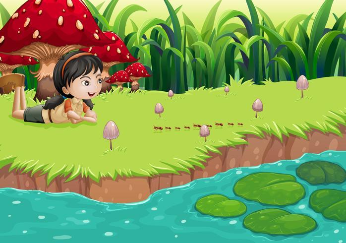 Una niña en la orilla del río cerca de las setas rojas