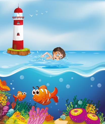 Ein Junge, der am Strand mit einem Leuchtturm schwimmt