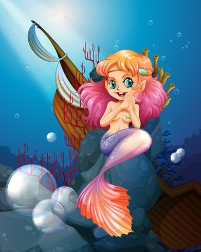 Eine hübsche Meerjungfrau unter dem Meer in der Nähe der Felsen