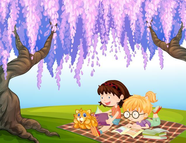 Filles lisant au parc avec un chat
