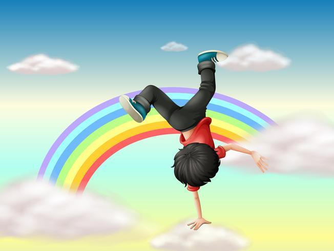 Um menino que executa uma dança de ruptura ao longo do arco-íris
