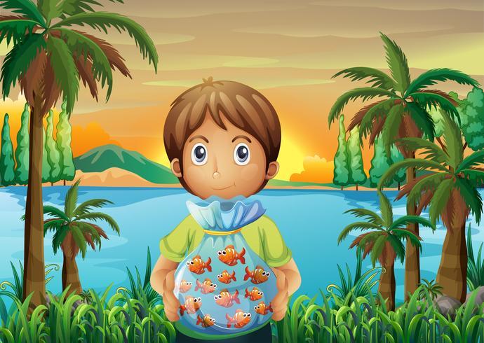 En pojke som står nära floden och håller en plast fisk