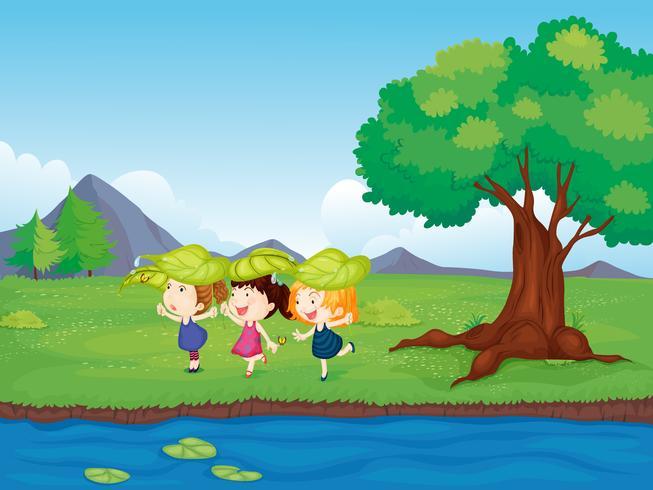 Drie meisjes die naast de vijver spelen