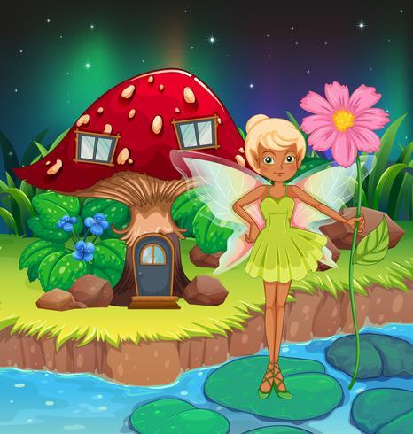 Un hada sosteniendo una flor cerca de la casa de setas rojas