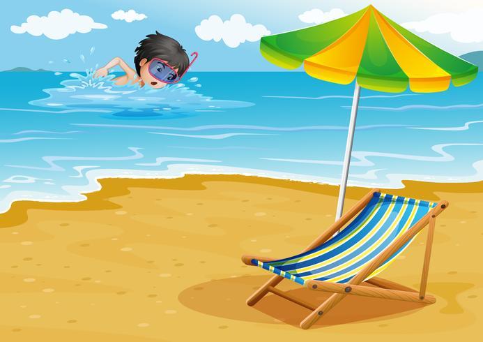Een jongen die op het strand met een paraplu en een opvouwbaar bed zwemt