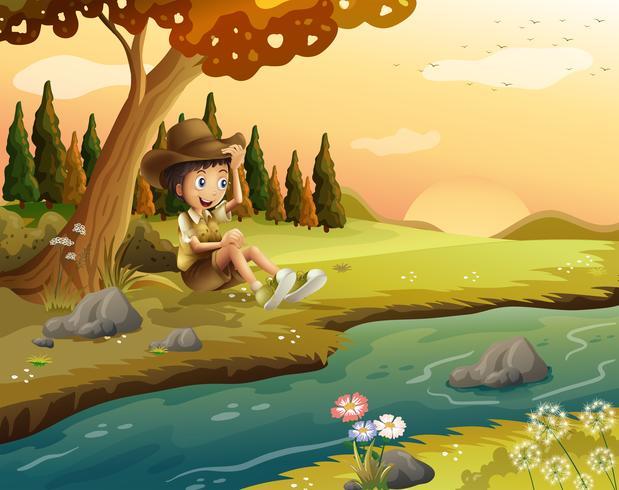A boy sitting at the riverbank