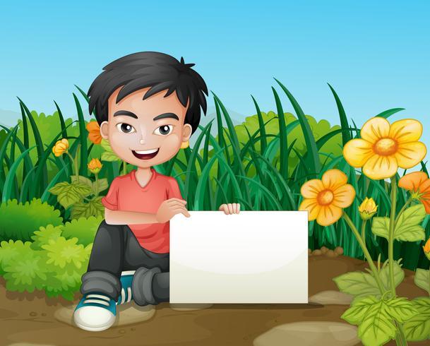 Un ragazzo sorridente che tiene un contrassegno vuoto nel giardino