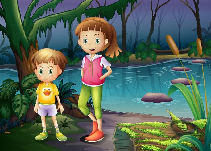 Un niño y una niña de pie en medio del bosque.