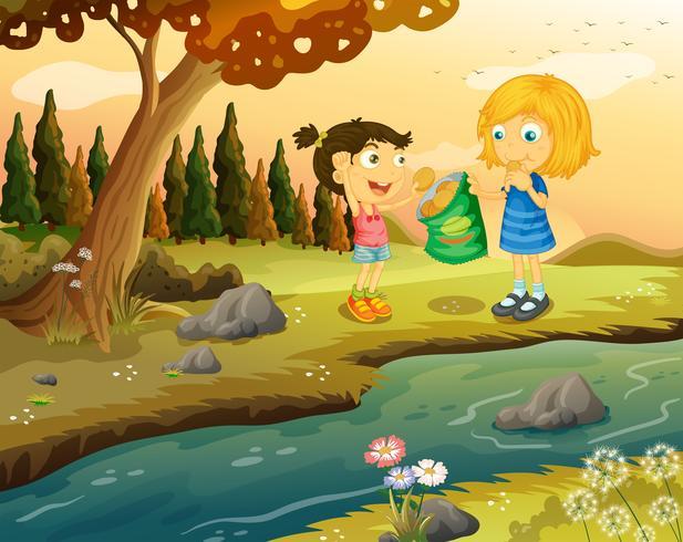 Dos chicas comiendo comida chatarra en la orilla del río