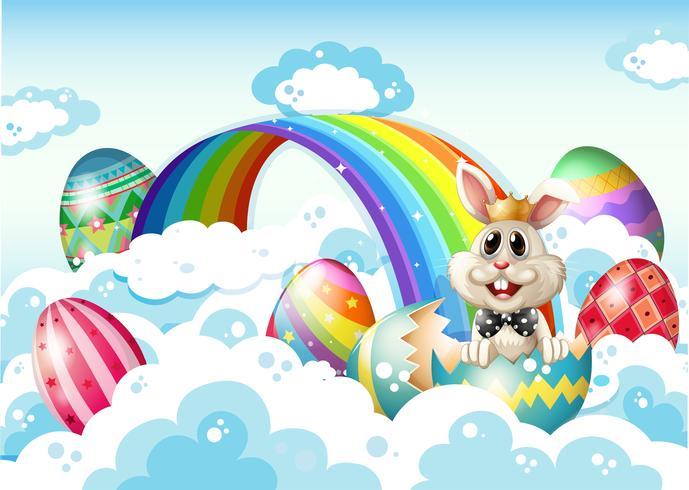 Un re coniglio nel cielo con le uova di Pasqua vicino all'arcobaleno