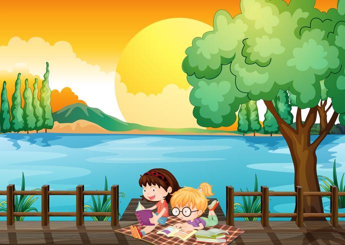 Dos chicas estudiando en el puente de madera.