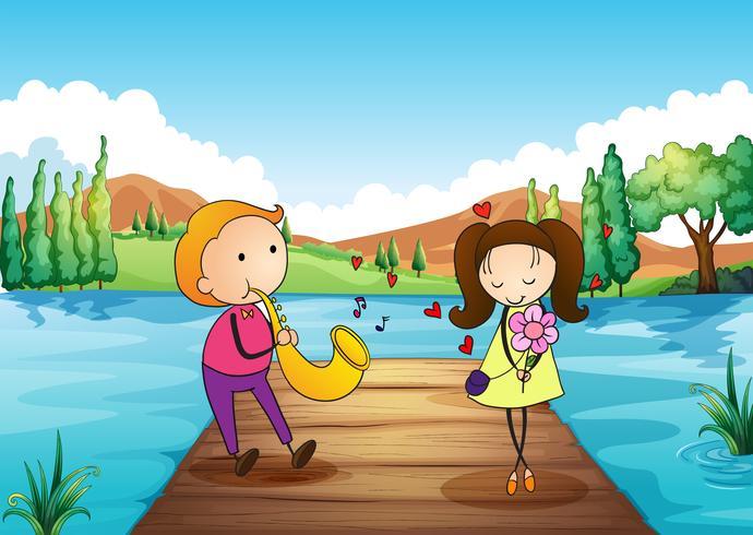 Un giovane uomo che serena la sua ragazza sulla riva del fiume