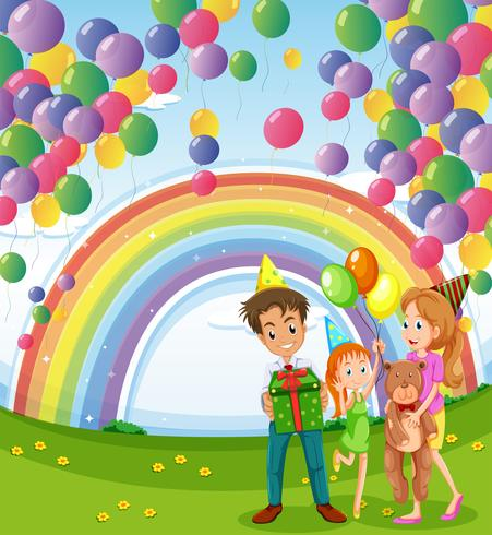 A family below the floating balloons with a rainbow
