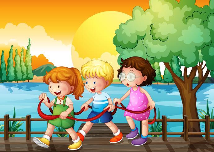 Tres niños jugando dentro de la cinta en el puente de madera
