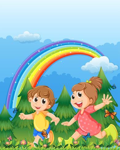 Niños jugando cerca del jardín con un arco iris en el cielo.