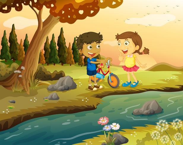 Un niño y una niña con una bicicleta en la orilla del río.