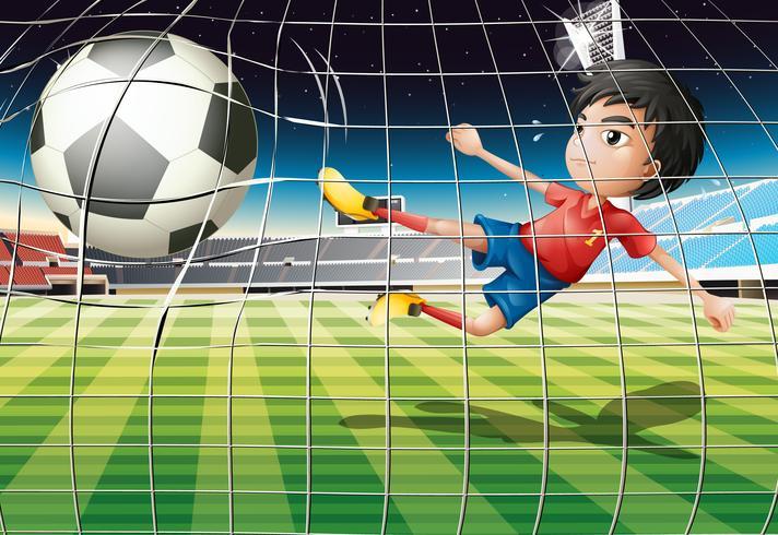 Un ragazzo che calcia la palla al campo di calcio