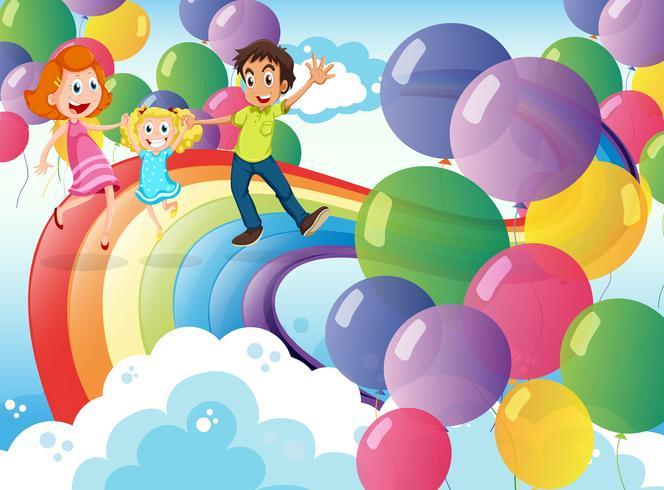 Una familia feliz jugando con el arco iris y los globos flotantes.