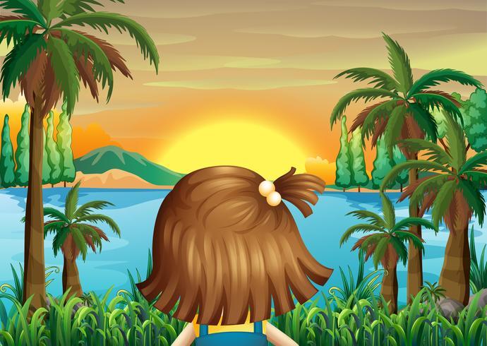En liten tjej som tittar på solnedgången vid flodbredden