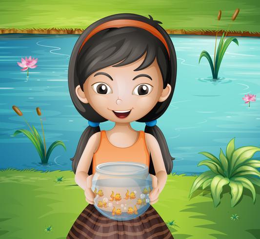Een glimlachend jong meisje dat een aquarium houdt
