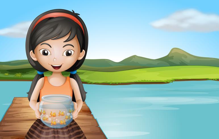 Una niña con un acuario de pie en el trampolín.
