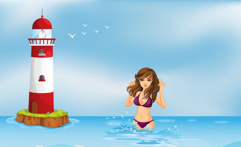 En tjej som bär en bikini på stranden bredvid ett torn