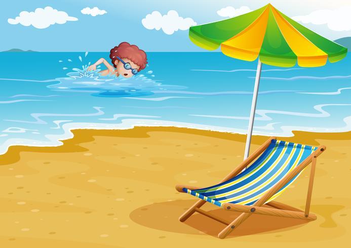 Un niño nadando en la playa con una silla y una sombrilla.
