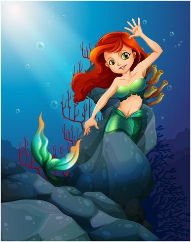 Una hermosa sirena atrapada con las grandes rocas bajo el mar