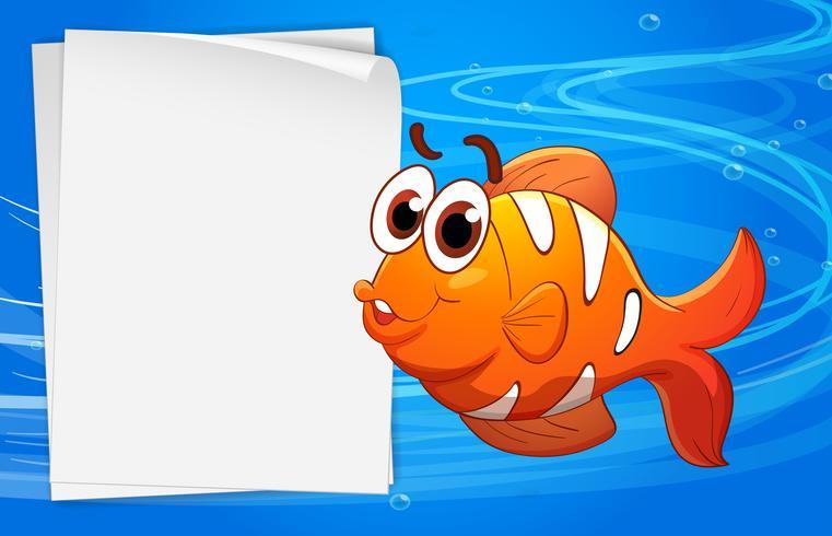 En apelsinfisk bredvid ett tomt papper under vattnet