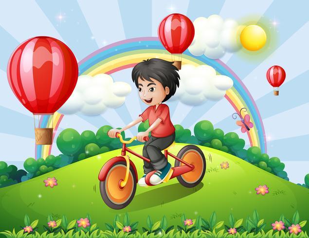 Een jongen die op de heuveltop fietst met een regenboog en zwevende ballonnen