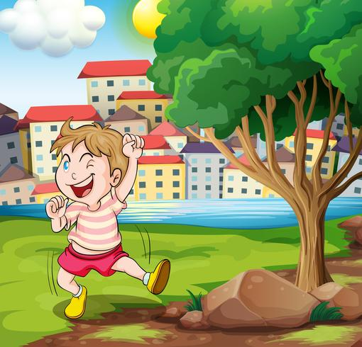 A happy kid near the tree at the riverbank beside the tall buildings