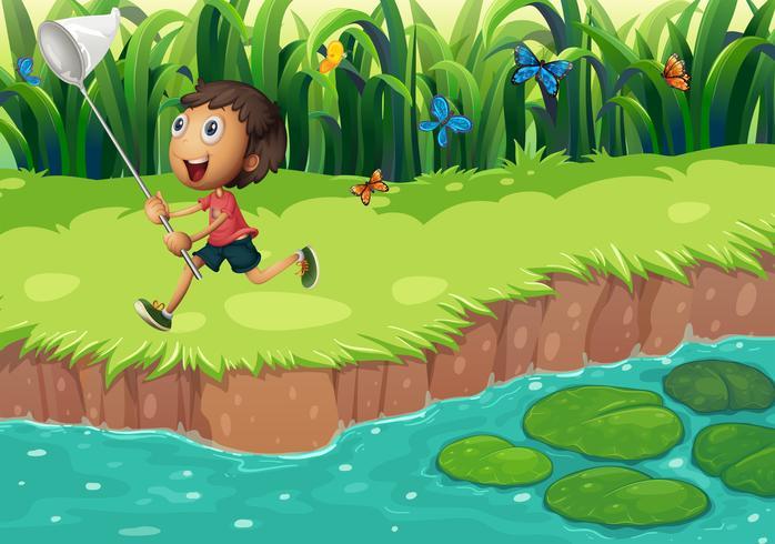 Ein Junge, der Schmetterlinge am Flussufer fängt
