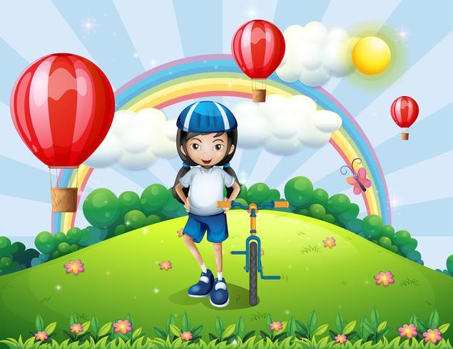 Een heuveltop met een meisje dat naast haar fiets staat