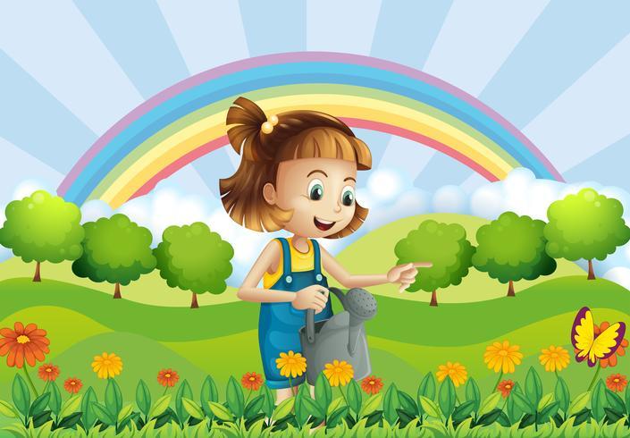 Une jeune fille tenant un arroseur dans le jardin
