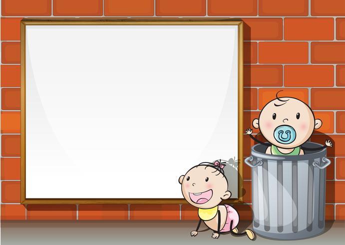 Los bebés cerca de la pared con un letrero vacío
